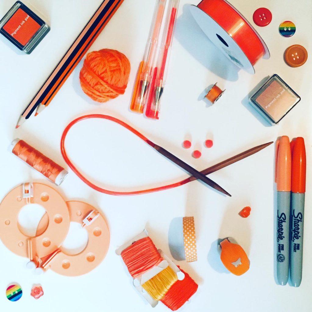 flatlay of craft supplies in shades of orange - craftic challenge pride month