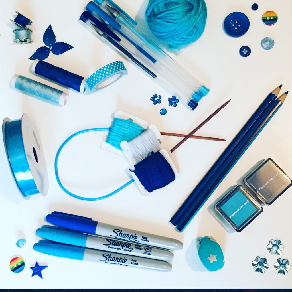 flatlay of craft supplies in shades of blue - craftic challenge pride month