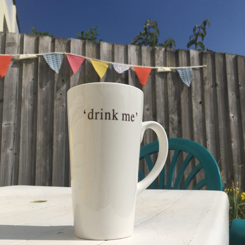 """Mug of Tea with """"drink me"""" slogan, outside with blue sky and bunting in the background"""