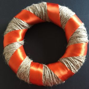 Bright orange ribbon wrapped around the wreath