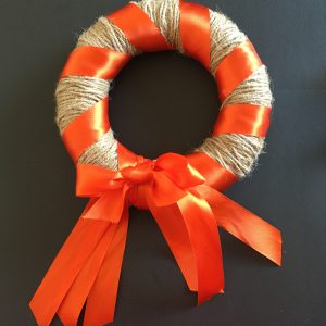Simple autumn wreath taking shape, with hessian twine, orange ribbon and an orange bow at the bottom